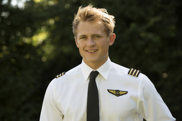 Portrait of a young airline pilot in uniform