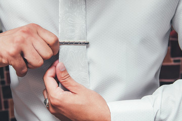 Man in white shirt putting on tie clip, closeup Fotobehang