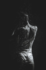 Shower. Girl in a white T-shirt standing under a shower. Black a