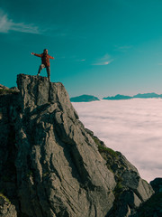 Toned image adult woman with a backpack with arms outstretched stands on the edge of a cliff and looking at the sunrise against the blue sky and thick clouds floating down