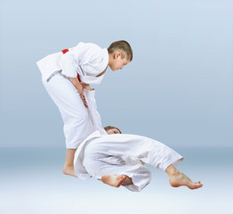 On a light background athletes train judo throws