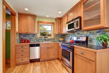Light brown kitchen cabinetry and brick tile back splash trim