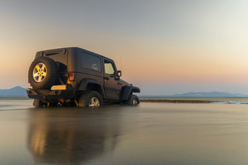 Car 4x4 in the mud doing sports against the sunset.