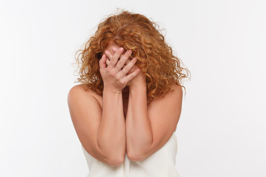 Picture of embarrassed mature woman in studio. Beautifulred haired lady closing her face with hands isolated on white background. Emotions concept.