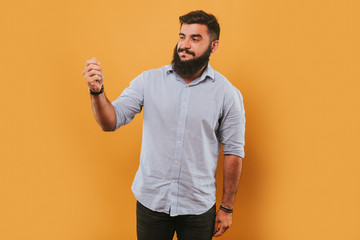 portrait of handsome smiling man isolated on yellow studio background posing to the camera and making funny faces and counting money