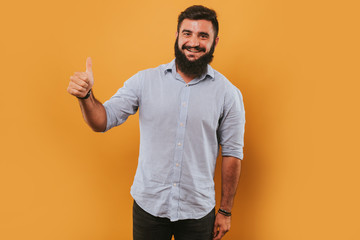 portrait of handsome smiling man isolated on yellow studio background posing to the camera and making funny faces and give likes