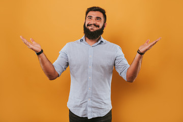 portrait of handsome smiling man isolated on yellow studio background posing to the camera and making funny faces, comparing with hands