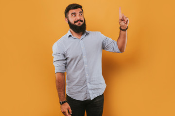 portrait of handsome smiling man isolated on yellow studio background posing to the camera and making funny faces got an idea