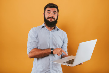 portrait of handsome smiling man isolated on yellow studio background posing to the camera and making funny faces, got idea, pointing to the monitor working on laptop computer