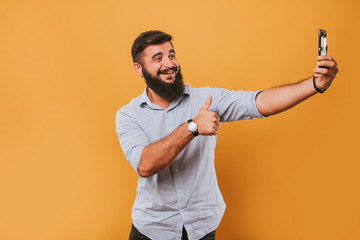 portrait of handsome smiling man isolated on yellow studio background posing to the camera and making funny faces and selfie