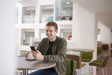 Young man using his smartphone in a modern university cafe