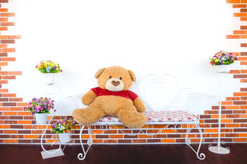 Teddy Bear toy alone on a iron chair with a decorate background.
