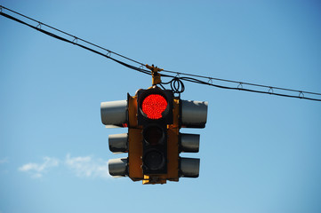 red traffic light hanging against sky
