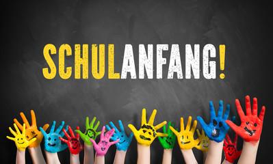 lachende angemalte Kinderhände vor Kreidetafel mit dem Wort Schulanfang!