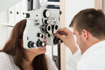 Male Optometrist Adjusting Phoropter While Examining Patient