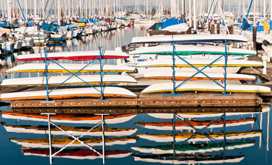 Foto op Plexiglas Water Motor sporten Colorful Kayaks Stacked on a Pier at a Marina north of Seattle and Reflected in the Water