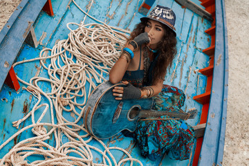 Atrractive young hippie woman with guitar sitting in old boat