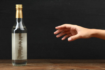 Bottle with alcohol drink on a dark background. The concept of alcoholism