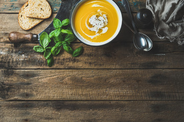 Pumpkin cream soup in bowl with fresh basil, spices and grilled bread slices over old rustic wooden background, top view, copy space, horizontal composition