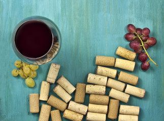 Glass of red wine with grapes, corks and copyspace