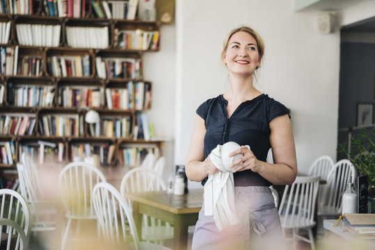 Smiling woman drying cup in a cafe