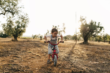 Little boy with children's bike on a field