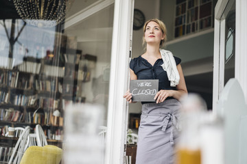 Woman in a cafe holding closed sign