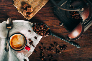 Closeup of mug with black coffee and a coffee mill
