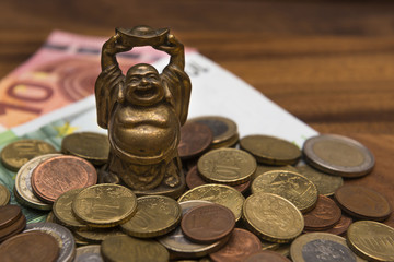Mascot netske Hotei coins Euro banknotes on a wooden table