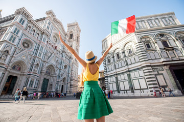 Young female traveler standing with italian flag in front of the famous Santa Maria del Fiore cathedral in Florence. Promoting tourism in Italy