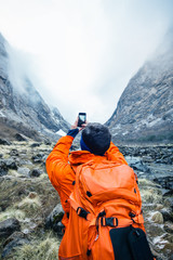 Tourist taking photo of Himalayan gorge