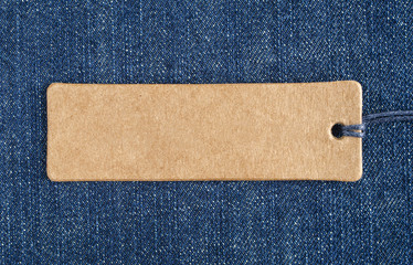 Blank paper label on a blue denim fabric. Jeans background with sale or price tag.