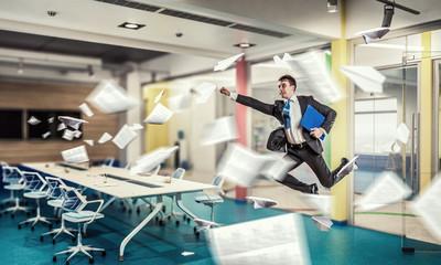 Fototapeta Jumping businessman in office . Mixed media