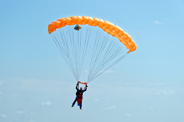 Paraglider flying on orange-colored parachute in blue clear sky at a bright sunny summer day. Active lifestyle, extreme hobbies