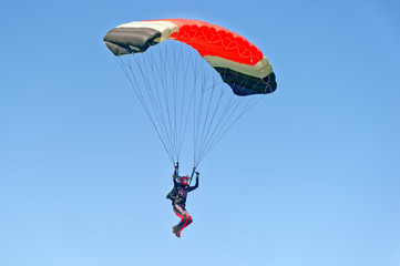 Paraglider flying on colorful parachute in blue clear sky at a bright sunny summer day. Active lifestyle, extreme hobbies