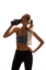 Beautiful sportive girl holding bottle, posing over white background.