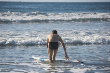 Atheltic muscular man with swimsuit trunks guiding surfboard in shallow water from behind