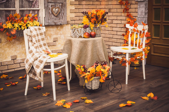 A cozy patio. Autumn leaves lying on the wooden floor, at the center are two white chairs and a table with burlap, fruits and a vase of berries and foliage. Background is brick wall and vintage window