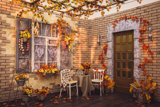 Patio. Shutters of the window and brick walls decorated with autumn garlic, pepper, corns and yellow leaves. There are two chairs, table with fruits in frame.