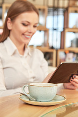 Web surfing. Selective focus on the cup on the cafe table cheerful woman using digital tablet on the background