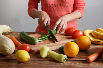 Woman is cutting cucumber for salad on wooden board