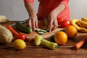Woman makes salad from cucumber and other vegetables