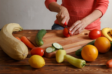 Woman is cutting tomatoes for salad on wooden board