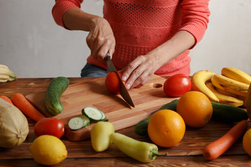 Girls is cutting tomatoes for sauce on wooden board