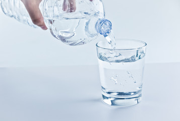 filling a glass with water through bottle, nutrition and health-care concept