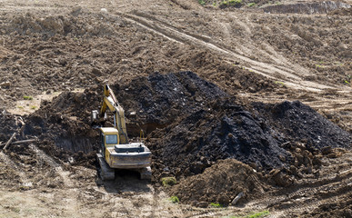 Excavator performs earth works. Construction of road in mountainous terrain.