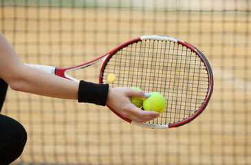 tennis racket with ball on clay court