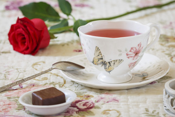 Fruit tea in a porcelain dish, chocolates and red rose