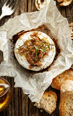 Baked Camembert with walnuts, honey  and rosemary on wooden rustic table, top view