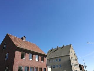 Alte Wohnhäuser mit spitzen Giebeln vor blauem Himmel am Mittelhafen von Münster in Westfalen im Münsterland